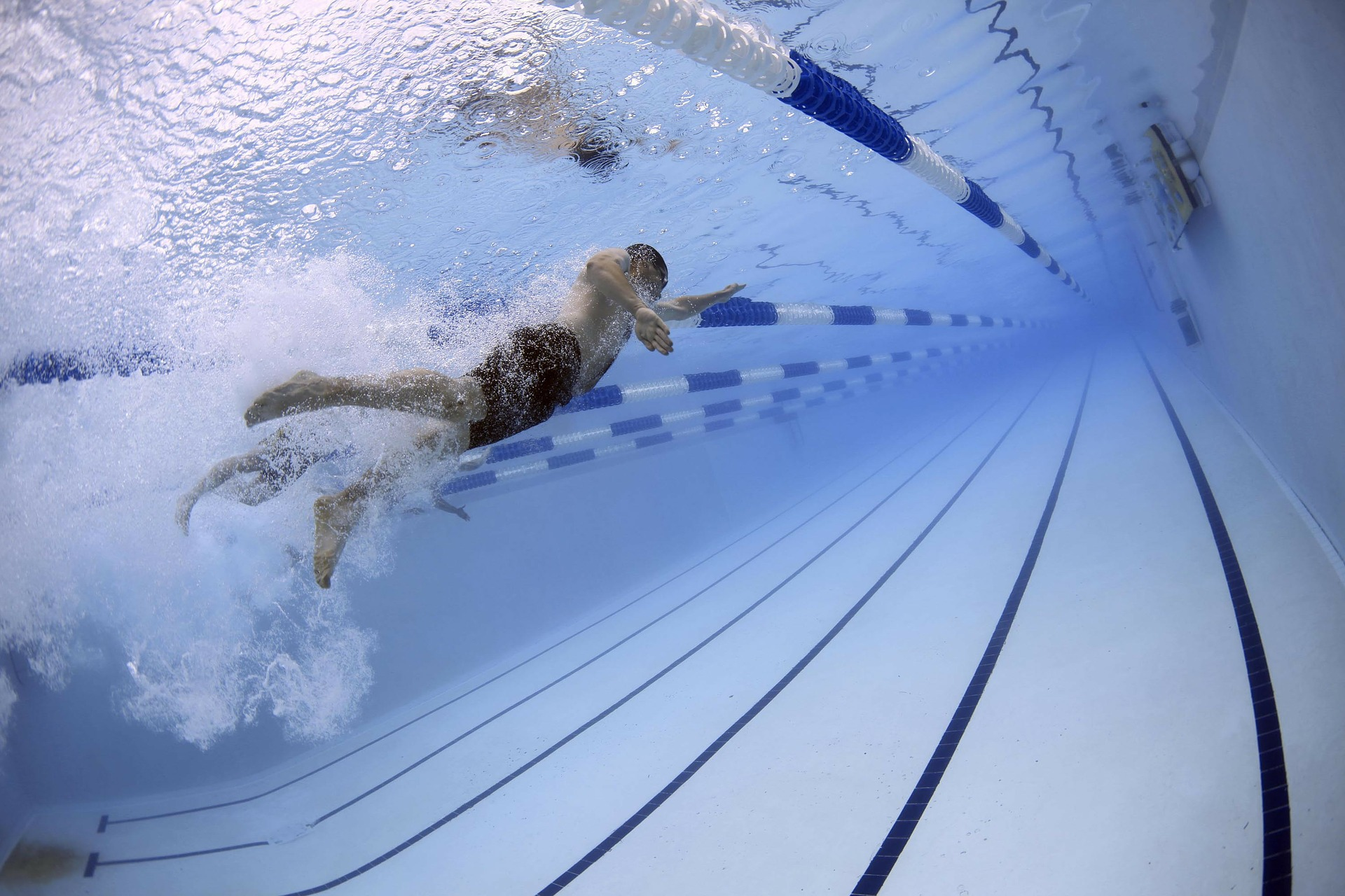 a person in a swimming pool, underwater, racing